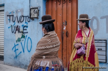 Cholitas in the street in front of a political message in the wall, El Alto, Bolivia